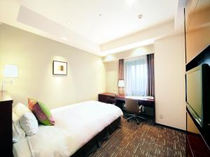A bed or beds in a room at Akita Castle Hotel