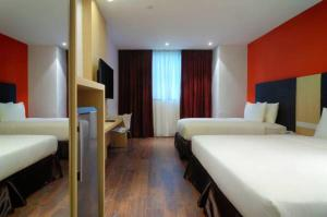 A bed or beds in a room at The Klagan @ Riverson Hotel