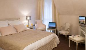 A bed or beds in a room at Logis Hotel Le Parc & Spa