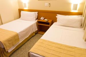 A bed or beds in a room at FlatGyn Paineiras