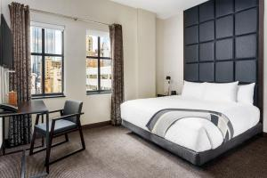 A bed or beds in a room at Distrikt Hotel Pittsburgh, Curio Collection by Hilton