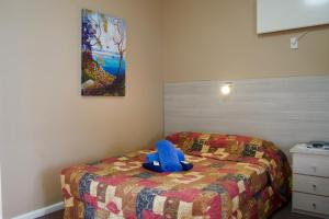 A bed or beds in a room at Norfolk Pine Motel