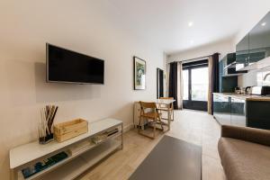 A television and/or entertainment centre at Chez Nous - 7 Appartements sur le Vieux Port