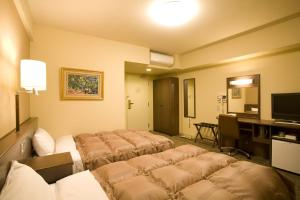 A bed or beds in a room at Hotel Route-Inn Omagari Ekimae