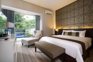 A bed or beds in a room at Grand Kecubung Hotel