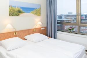 A bed or beds in a room at Hotel Astor Kiel by Campanile