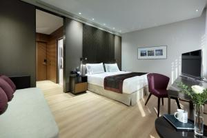 A bed or beds in a room at Eurostars Torre Sevilla