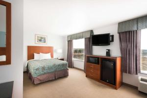 A television and/or entertainment centre at Days Inn by Wyndham Evans Mills/Fort Drum
