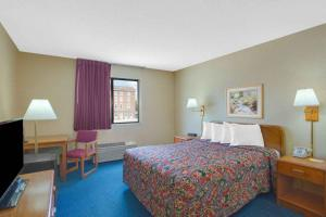 A bed or beds in a room at Days Inn by Wyndham Auburn/Finger Lakes Region
