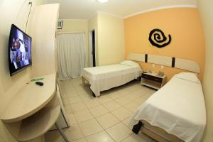A bed or beds in a room at San Manuel Praia Hotel