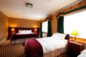 A bed or beds in a room at Riverbank House Hotel