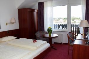 A bed or beds in a room at Hotel Seeblick garni
