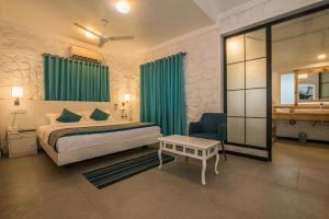 A bed or beds in a room at The Tamarind Hotel Anjuna