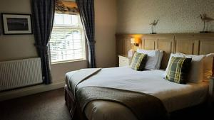 A bed or beds in a room at Queens Head Inn & Restaurant