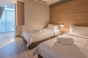 A bed or beds in a room at Jinhold Hotel & Serviced Apartment
