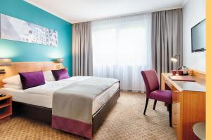 A bed or beds in a room at Leonardo Hotel Düsseldorf City Center