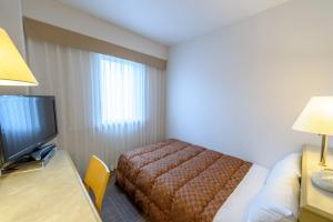 A bed or beds in a room at Court Hotel Mito