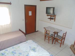 Uma TV ou centro de entretenimento em Chales Marigu