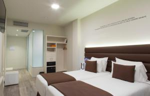 A bed or beds in a room at Bcn Urbaness Hotels Gran Rosellon