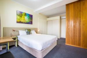 A bed or beds in a room at Boomerang Hotel