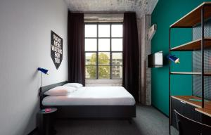 A bed or beds in a room at The Student Hotel Maastricht