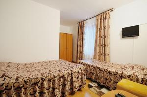 Un pat sau paturi într-o cameră la Pensiunea Claudia