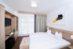 A bed or beds in a room at Terrassenhotel Reichmann