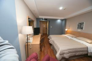 A bed or beds in a room at Athina Airport Hotel