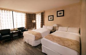 A bed or beds in a room at Riviera Hotel on Robson Downtown Vancouver