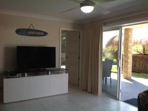 A television and/or entertainment center at Mollymook Apartment on Golf