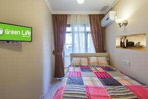A bed or beds in a room at Green Life Apart Hotel