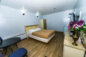 A bed or beds in a room at New Plaza Motel