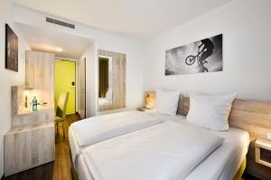 A bed or beds in a room at Novina Sleep Inn Herzogenaurach