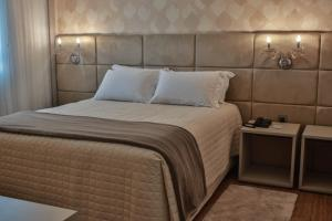 A bed or beds in a room at Interclass Hotel Criciuma