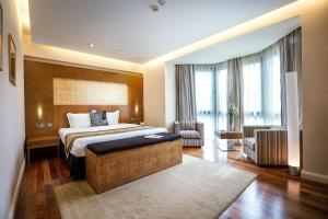 A bed or beds in a room at The Dostyk Hotel