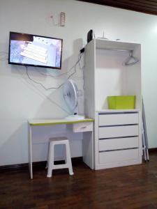 Una televisión o centro de entretenimiento en Ajuricaba Suítes 7