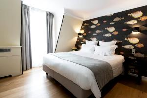 A bed or beds in a room at Hôtel Mathis Elysées