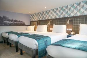 A bed or beds in a room at Best Western Plus London Croydon Aparthotel