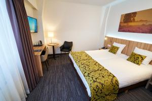 A bed or beds in a room at Amrâth Hotel Lapershoek Arenapark