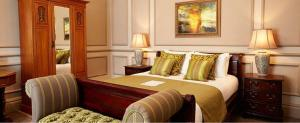 A bed or beds in a room at Cedars Inn by Greene King Inns