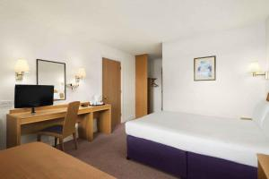 A bed or beds in a room at Days Inn Kendal - Killington Lake