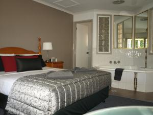 A bed or beds in a room at Old Coach Motor Inn Echuca