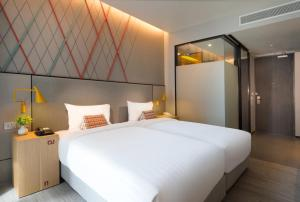 A bed or beds in a room at ibis Styles Bangkok Sukhumvit Phra Khanong