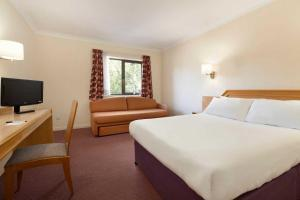 A bed or beds in a room at Days Inn Southampton Rownhams