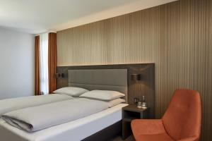 A bed or beds in a room at H4 Hotel Residenzschloss Bayreuth