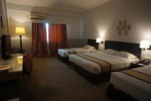 A bed or beds in a room at Tyng Garden Hotel