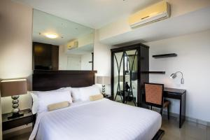 A bed or beds in a room at Kuta Reef Apartments