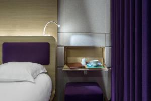 A bed or beds in a room at Hôtel Odyssey by Elegancia