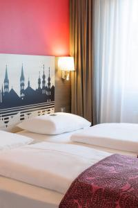 A bed or beds in a room at Mercure Hotel Würzburg am Mainufer