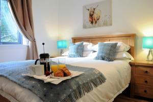 A bed or beds in a room at Bluebell Cottage with Hot Tub